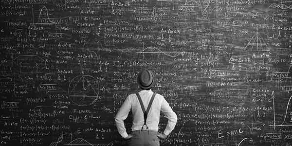 Man in front of a giant chalkboard with equations filling it.