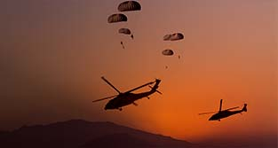 Airborne soldiers parachuting from a plane against an amber sunset